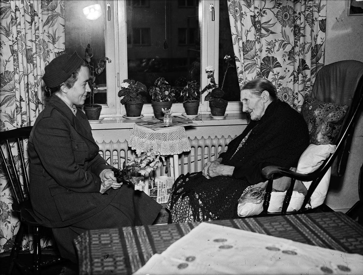 Åldrig kvinna i gungstol, samtalar med yngre kvinna, Uppsala 1946