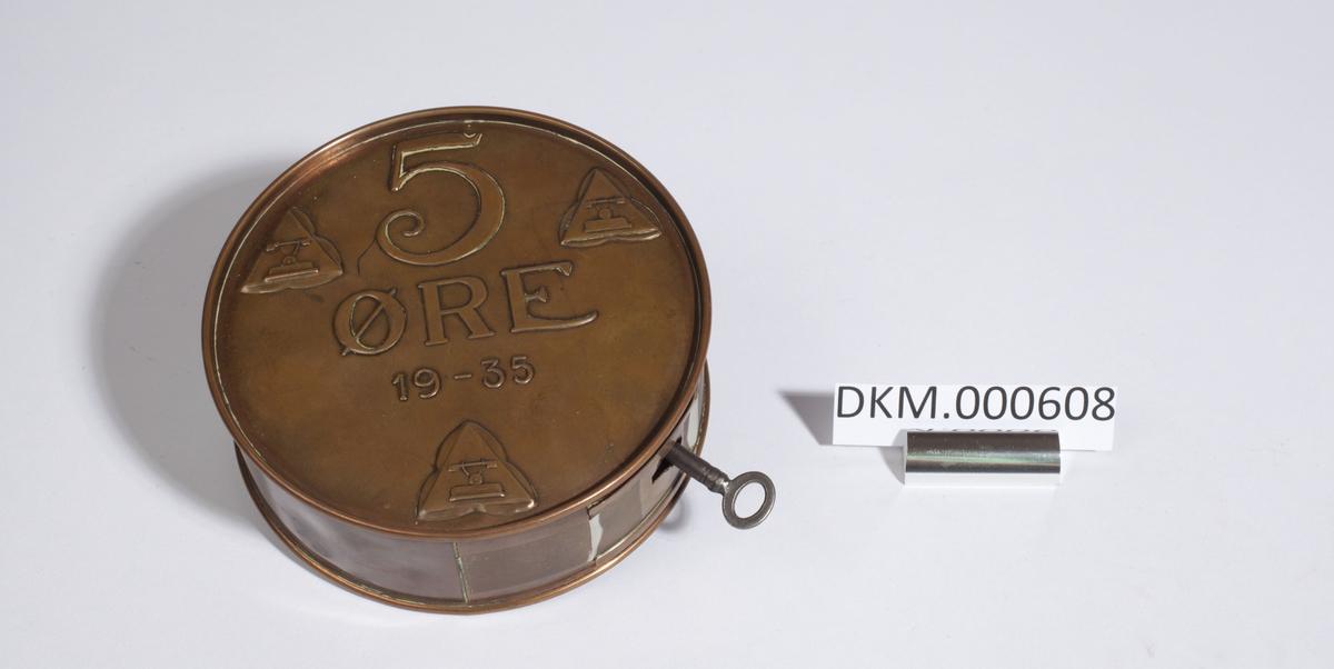 Flat, rund sparebøsse. Toppen etterlikner en 5 øres mynt fra 1935.