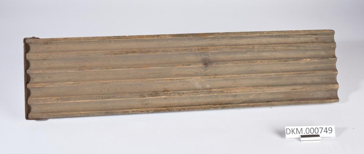 Avlang planke med fem langsgående riller, det er kanter som er litt høyere enn rillene langs begge langsider og en kortside, på den andre kortsiden er ett jernbeslag som er festet med seks skruer.