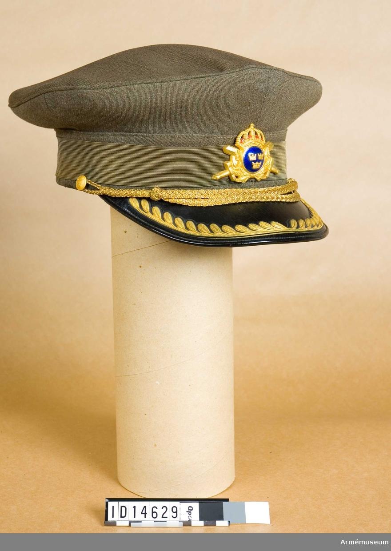 Skärmmössa av platt typ är tillverkad av gråbrungrönt ylletyg med svartlackerad skärm med lagerkrans m/1952, mössrem m/1952 och två små knappar m/1952 för dess fästande  samt mössmärke m/1952 (krönt trekronorsvapen över två korslagda svärd). Insidan fodrad med bomullsatin och märkt med firmamärket MEA Stockholm.