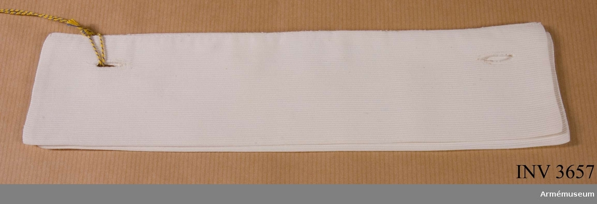 Manschett till lottaklänning i bomull, grå, SLK. Sydd dubbel i vit piké. Två handsydda knapphål i vardera långsidas yttre kant. Skall knäppas på klänningens manschettknappar, det vill säga den  undre knäppningen. Längd 195-215 mm, bredd 57 mm.