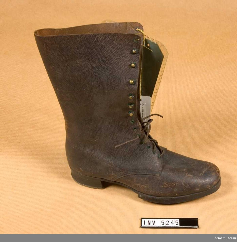 Brun läderkänga med högt skaft och snörning. Klacken är järnskodd.