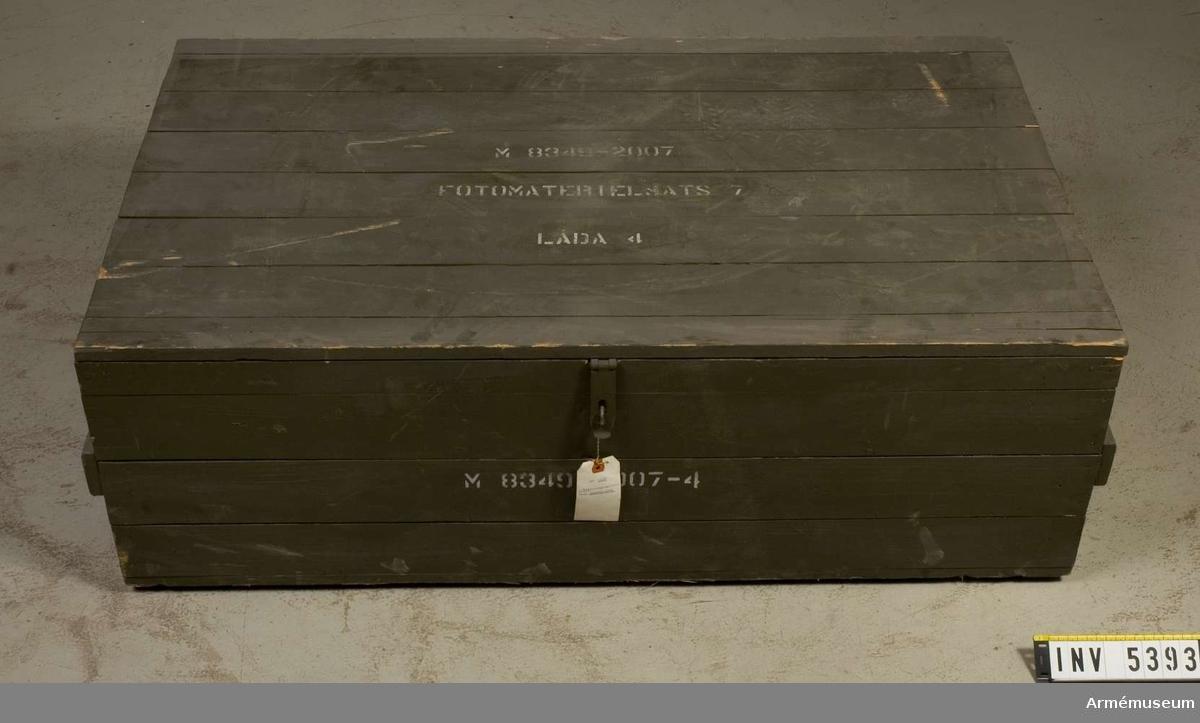 Förvaringslåda av grönmålat trä. Locket är märkt: M8349-2007 Fotomaterielsats 7 Låda 4.På lågsidan märkt med vit text, framställd med schablon: M8349-2007-4 .