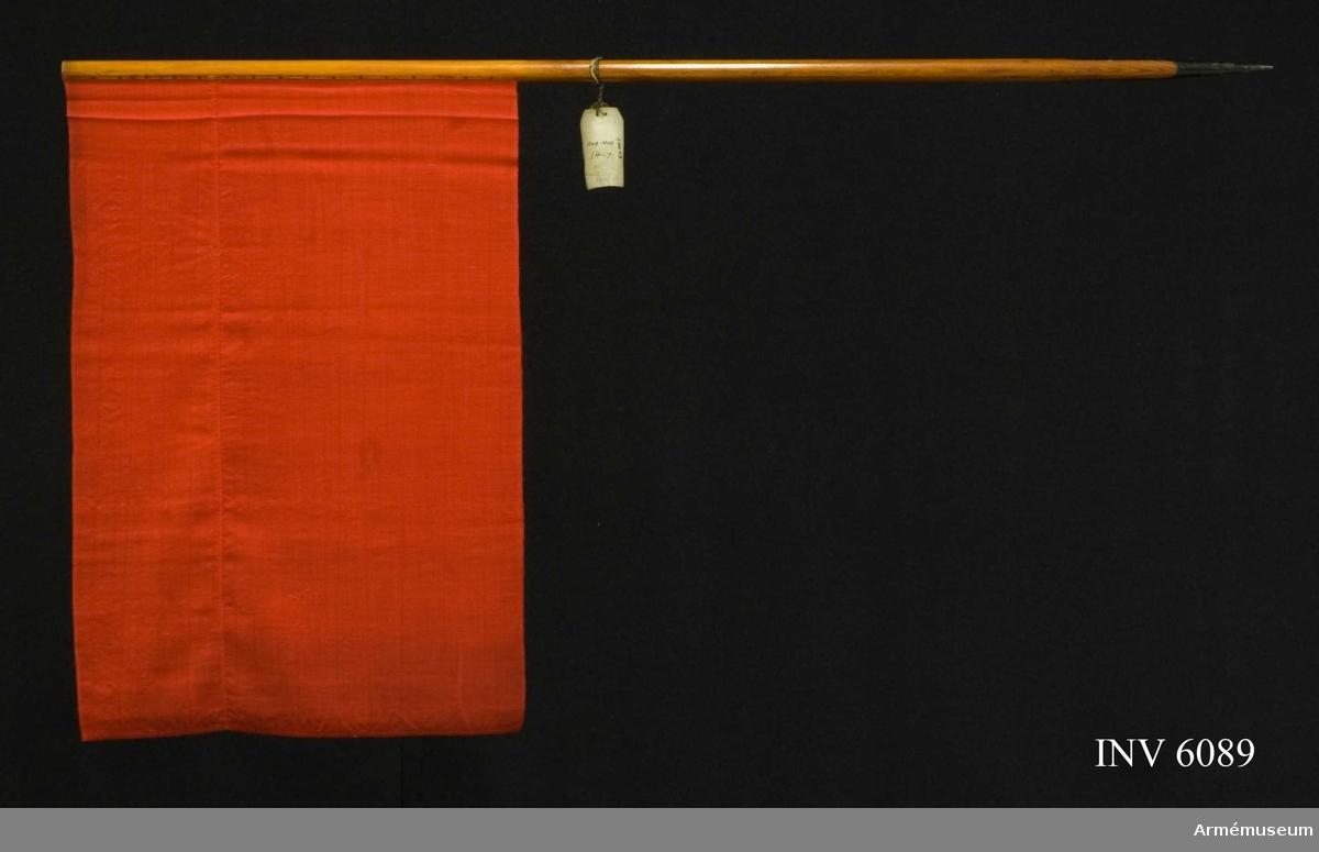 """Röd ylleflagga utan dekor. Vådbredd 450 mm. Smutsig. Tvättad i vatten. Text på vidhängande lapp: """"Arbetsmodell å Signalflagga, röd i likhet med den af Generalfälttygmästaren och Chefen för artilleriet den 13 maj 1895 fastställda modellen. Stockholm den 27 December 1896 Otto Wirgin Fälttygmästare"""". Tillh. fodral m läderrem AM 53/726 m/1897.  Samhörande nr är 5828-5899, 6000-6099, 6200-6212."""
