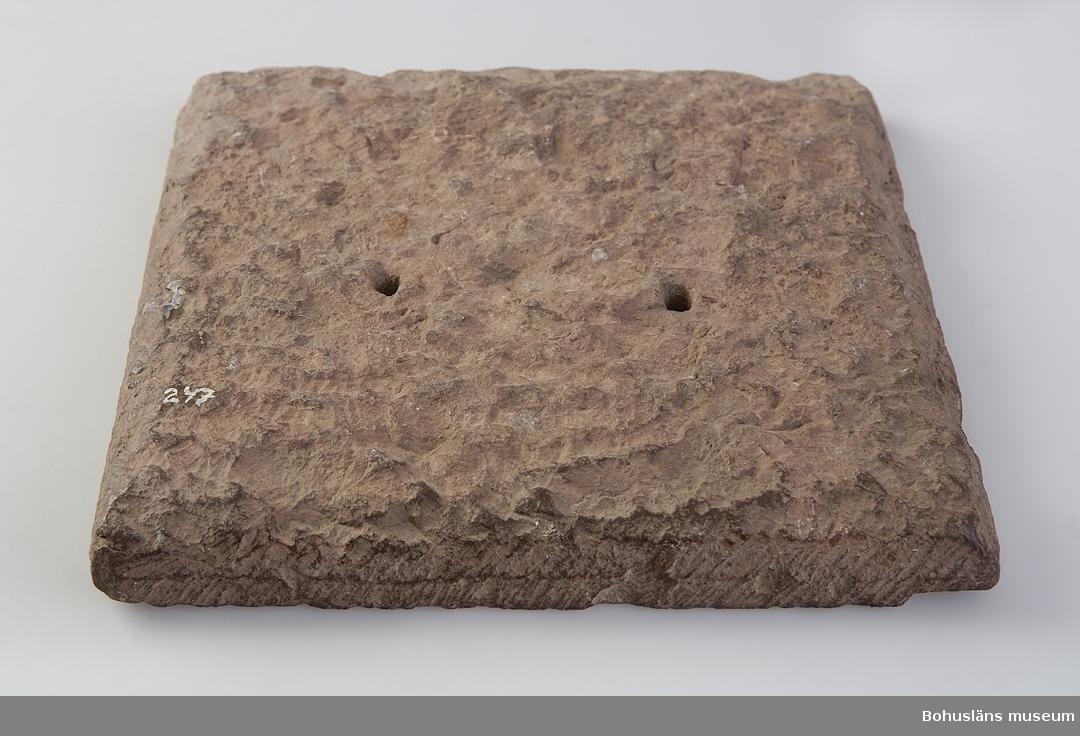"""Ur handskrivna katalogen 1957-1958: Solur, av rödgrå kalksten. Mått: 23,5 x 23,5 x 3 cm; m. 3 hål f. visaren, vilken saknas; """"1705""""; Västergötland. Små bitar avslagna.  Ur Knut Adrian Anderssons katalog 1916: No 2 Ett solur av rödgrå kalksten, med 3 hål till plats för visare, som här saknas. (23,5 x 24 cm) Från Väster- Götland 1705. Varit uppsatt på Krokstads kyrkogård. Inköptes 18 Februari 1903 fr. Fröken Stenström.  Krokstad kryrka av sten med torn och med tresidig avslutning i öster byggdes 1861 - 1863 och ersatte en medeltida stenkyrka. Dopfunten av trä härrör från 1600-talet."""