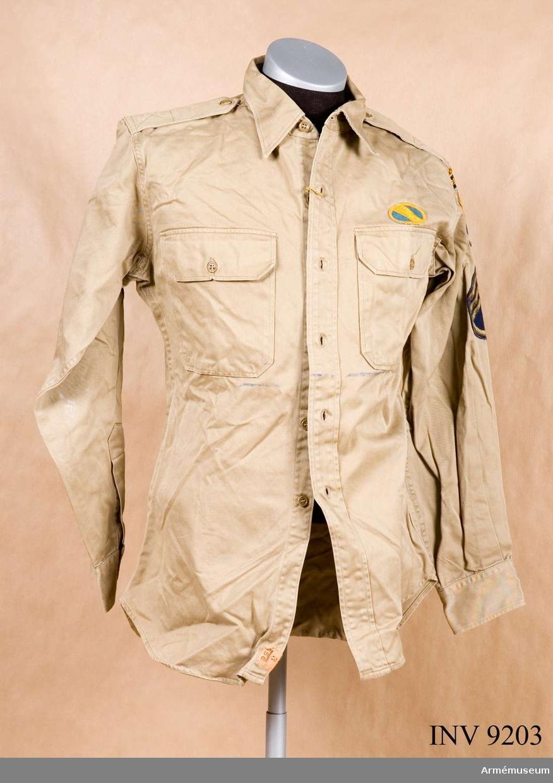 """Skjorta, Special Forces U S Army 1960, sergeant. Sydd i grågrön (beige) bomullskhaki, ett impregnerat tyg. Två bröstfickor med lock och knäppning, krage på stånd och enkla manschetter. Skjortan har ok i ryggen och fasta axelklaffar. På vänster sida strax ovanför fickan ett ovalt gult och blått märke. På vänster överärm överst ett märke där det står RANGER. Under det ett märke där det står AIRBORNE. Under det ett granatformat märke, blå botten och ett gult svärd med tre blixtar (Special forces insignier). Under det gradbeteckningen för sergeant. På höger överärm samma grabeteckningsmärke. Skjortan är nedtill på avigsidan märkt """"K 6895. Edmund Kolby, 626 Coral Way, Florida 33134"""". Källa: Army Badges and insignia since 1945 Book one. Blandford Colour Series."""