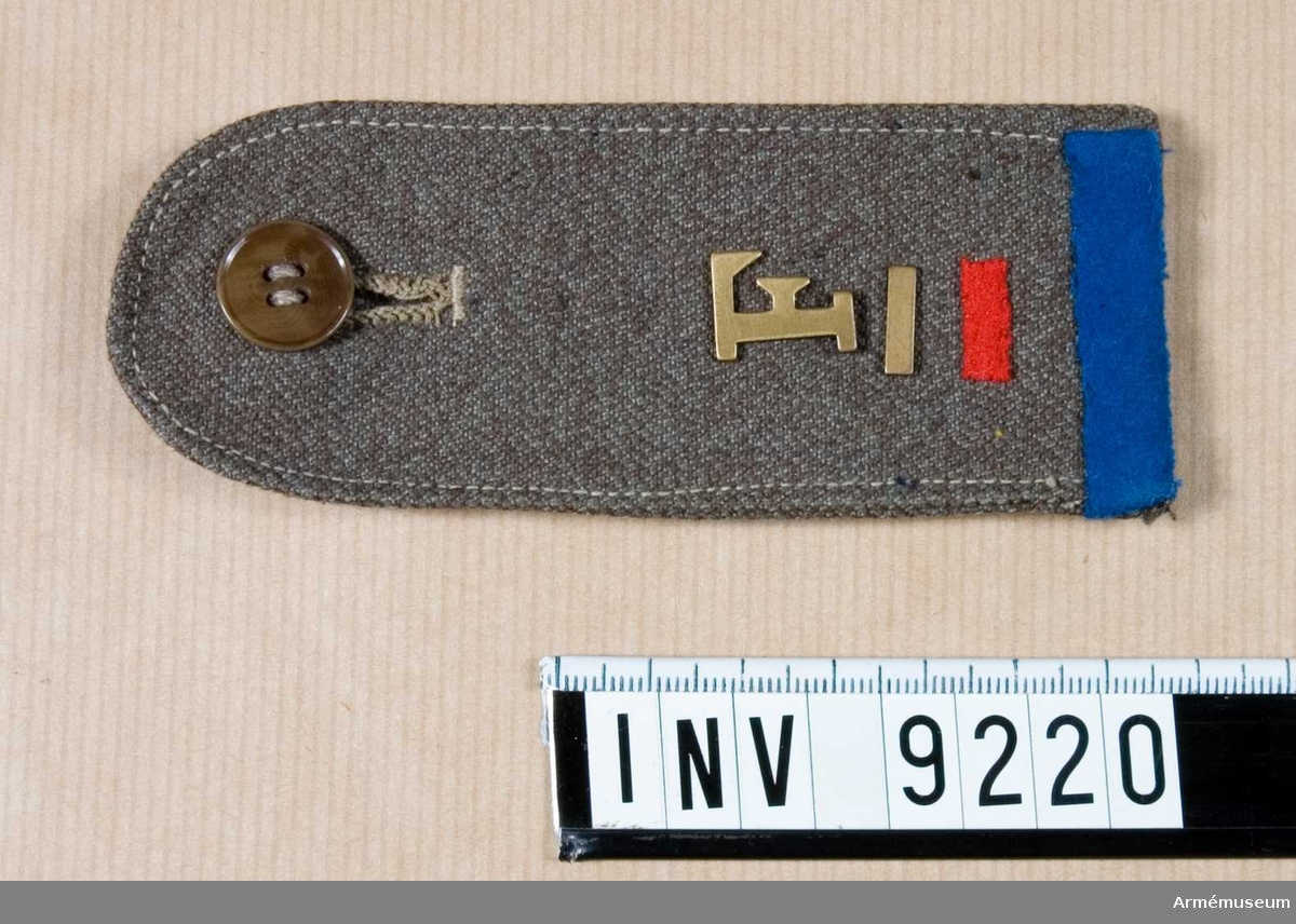"""Förplägnadstjänst m m, SLK.Av impregnerat bomullstyg s k """"plåttyg"""". Med tjänstegrenstecknet """"F"""" för förplägnadstjänst i bronsfärgad metall. Under detta en 10 mm stav av bronsfärgad metall vilket betecknar menigs tjänsteställning. Under detta en röd tvärställd stav vilket betecknar sjukvårdstjänst. Det blå bandet vid axelklaffens bas är beteckning för  funktionär av något slag. På undersidan finns en hank för fastsättning vid plagget.Källa: SLK Bestämmelser för Funktionärsbeteckningar m m."""