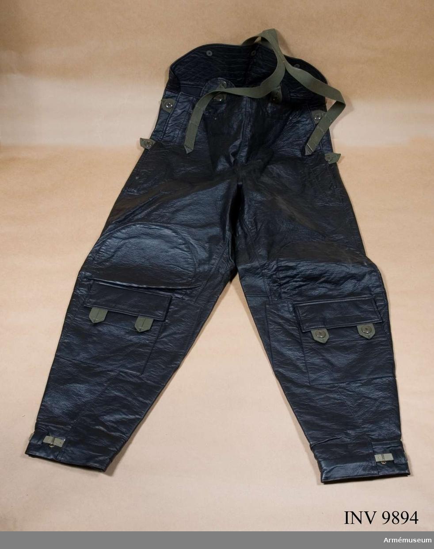 Motorbyxor fm/1940. Av svart konstläder med gröna hängslen och tampar. Bakstycket är förhöjd. Rem nedtill på benen.