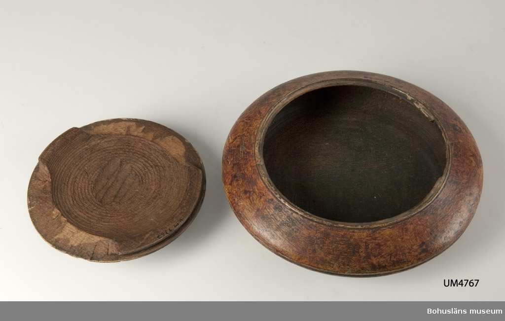 """571 Användningstid 1800-1944?  Rund, svarvad med lock. Locket har en rektangulär knopp mittpå. Locket låses med en vridanordning. En """"V"""" markering visar när det är öppningsbart. Linjedekor på lock och nederdel samt marmorerad i rödbrun färg. Har mörknat inuti på grund av användning.  Litt.; Nylén, Anna-Maja, Hemslöjd, Håkan Ohlssons förlag, Lund, 1978, s. 345-349.  Ur handskrivna katalogen 1957-1958: Träask Största diam: 20, Bikoniskt runt träkärl med lock, rödmålat. Föremålet helt  Lappkatalog: 84"""