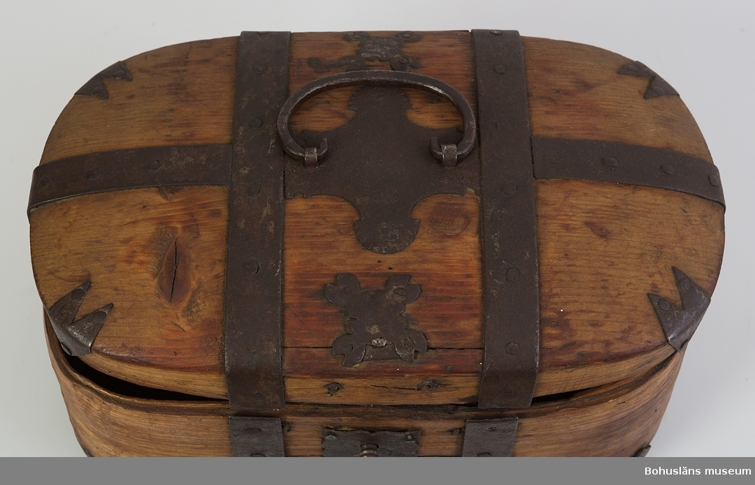 """Oval i svepteknik med välvt lock och botten. Konstruktionen hålls ihop av smidda järnband. Alla """"hörn"""" har dekorativa smidda beslag. Lock och nederdel sitter ihop med gångjärn. Mittpå locket finns ett handtag fästat. Fyrkantig nyckelskylt med vågformad kant. Lås i original. Nyckel finns.  Litt.; Granlund, John, Träkärl i svepteknik, Nordiska museets handlingar 12, s. 87-104.  Ur handskrivna katalogen 1957-1958: Tina, järnbeslagen L. 32, Br. 20 H. 17 cm; oval, 4 runtomgående järnband; handtag på locket. Nyckeln b) L. 6,2 cm."""