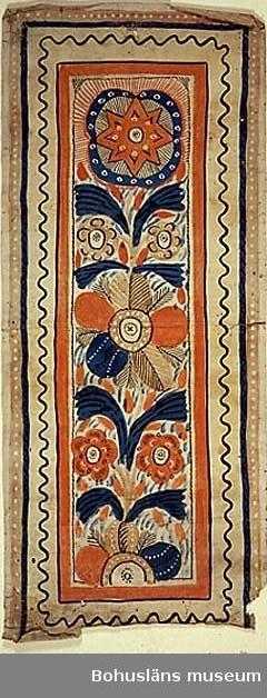 """Bonad målad på papper. Med samma mönster som UM004888, motiv med stiliserade blommor och en stjärna. Mellan blommorna fjäderliknande mönsterformer. Bårder med slingor och prickar. Färgerna i målningen är gulrött (orange),blått, beige, svart, vitt, mycket ljust gult. Enligt äldre katalog """"sk Tuppbonad fr Tutaryd i V Småland"""".  Lagad på baksidan med bitar av fastklistrad pappersremsa. Böjd och något trasig i kanten. Spikhål. Blekt. Smutsig mest i ena ändan. Spricka vid kanten mitt på. Oläslig blyertstext på framsidan.  Ur handskrivna katalogen 1957-1958: Väggbonad, s.k. Tuppbonad Mått c:a 1,20 x 0,50 m. Allmogemåln. på papper. Från Tutaryd V. Småland, början av 1800-talet. Ngt trasig."""