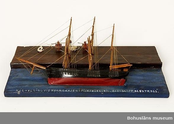 """Modell av kölhalning av tremastade barken Albatross på Kyrkokajen, Fiskebäckskil. Tillverkad av kapten John Emil Olsson (1880-1950), Fiskebäckskil på Skaftö i Lysekils kommun på 1940-talet. Trä, metall, lintråd, målat med oljefärg. Fartygsmodell längd 30 cm, bredd 4 cm, höjd 20 cm. Platta: 40 x 19 cm; okänd skala. Blockmodell målad i  svart och rött. Stående och löpande rigg. Däckshus och lastluckor. Monterad på en rektangulär platta med blåmålad vattenyta och brunmålad träkaj. Modellen ligger långsides med riggen nedhalad mot kajen. Två vinschspel på kajen fästade i fock- och stormast med två treskivade block i varje. Fällda rår. På modellens ovansida står textat med vita tryckbokstäver:  KÖLHALNING VID KYRKOKAJEN I FISKEBÄCKSKIL. BARKSKEPP. """"ALBATROSS"""". Kölhalning innebär att skeppet krängs på sidan så att skrov, botten och köl kan repareras och underhållas.  Definitioner: Bark - segelfartyg med tre eller fler master med rår på alla master och ett gaffelsegel på den aktra. Råsegel - rektangulärt eller trapetsformigt segel som förs på en rå, dvs. en horisontell stång fäst vid mastens framkant Gaffelsegel - trapetsformat segel fäst längs akterkanten av masten och med sina övre (kortare) och undre (längre) lik (kanter) fäst vid två rundhult (gaffel resp. bom).  Kyrkokajen eller Kyrkekajen, Fiskebäckskil: Under segelsjöfartens storhetstid på 1860- och 70-talen fylldes Kilen på vintern av fartyg som låg uppankrade hemmavid. Det var på vintern man hade möjlighet att se över och underhålla fartygen inför nästa seglationsperiod.  Epoken varade fram till 1930-talet då segelskutornas tid var förbi.  Vid Kyrkekajen ligger idag Skaftös skolsegelfartyg T/S Kvartsita.  Ur handskrivna katalogen 1957-1958: Kölhalning av """"Albatross"""" Modell på platta. Kölens mått 19,5 Föremålet helt. Från kapten Olssons saml., Fiskebäckskil.  För ytterligare information om John Emil Olsson och förvärvet, se UM005807.  Föremålet presenterat på Bohusläns museums hemsida år 2009 - 2013, webbutställnin"""