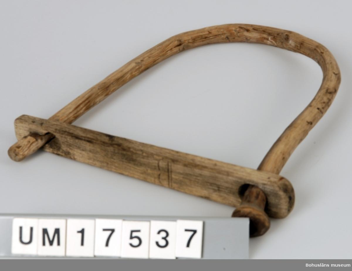 """Böjd (basad) gren. Ena sidan är fäst i ett runt hål i en träbricka. Den andra sidan är instoppad i ett nyckelhålsformat hål i samma bricka. Denna sida går att öppna. På var sin sida av brickan är det skuret """"B"""" respektive """"V"""". Föremålet trolien använt till att bära olika fiskeredskap. Föremålet kan vara en sk dörjeklåv avsedd för upphängning, och till att bära, dörjgrindar mm.  Litteratur: Haneson & Rencke, Bohusfisket, Göteborg 1923, sidan 175.  Ingår i redskapsbestånd ur sjöbod från Hällsö, Havstenssund, Tanum sn. Se UM17521."""