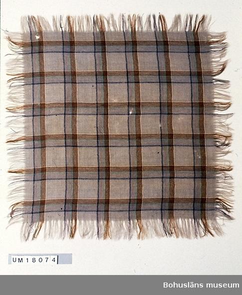 Kvadratisk scarf av ylle, vävd i gåsögon och rutig i två nyanser ljust brunt, mörkt gulgrönt, svart, beige och ljust blåtonat grönt. Fransar av varp och inslag. Troligen maskintillverkad eftersom rutorna är precis lika stora och väven är så jämnt slagen. Små hål här och var.  Använd av äldre släkting till givaren på 1930-40-talen. Se även UM018058.    även UM 610 18058. 990 Omkatalogiserat 1997-05-28 VBT