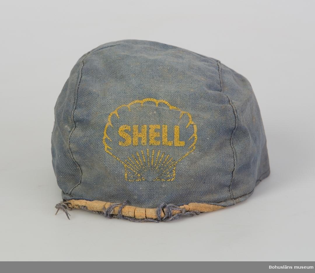 Skärmmössa i blått kypertväv tyg; skärmen saknas. Reklammössa för bensinmärket Shell, troligen använd sommartid i det dagliga arbetet på gården.