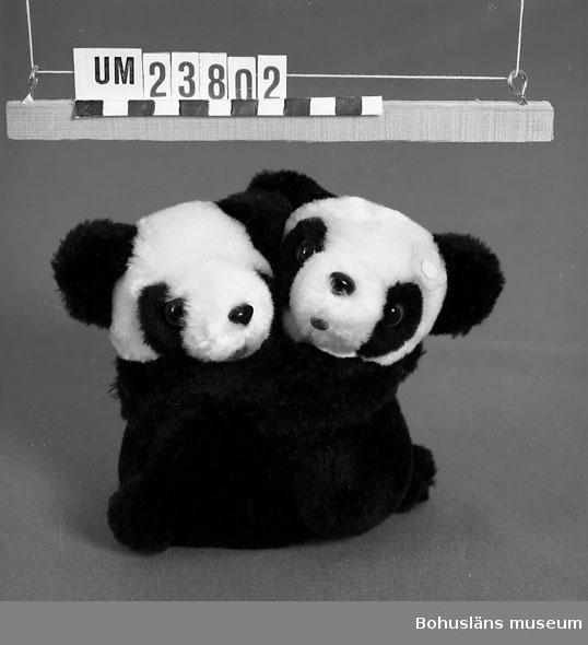 Två pandor som kramar varandra, hopsatt med kardborrknäppning, svarta med vita huvuden. På den ena en blomma av papper i rosa. Ögon av glas