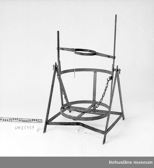594 Landskap BOHUSLÄN  A-formad stativ med rörlig del för att kunna fälla en damejeanne med syra el. dyl. Krage och kätting för fastsättning av damejeannen. Gråmålad, färgen delvis avslitet. Ersattes på 60-talet av plast.