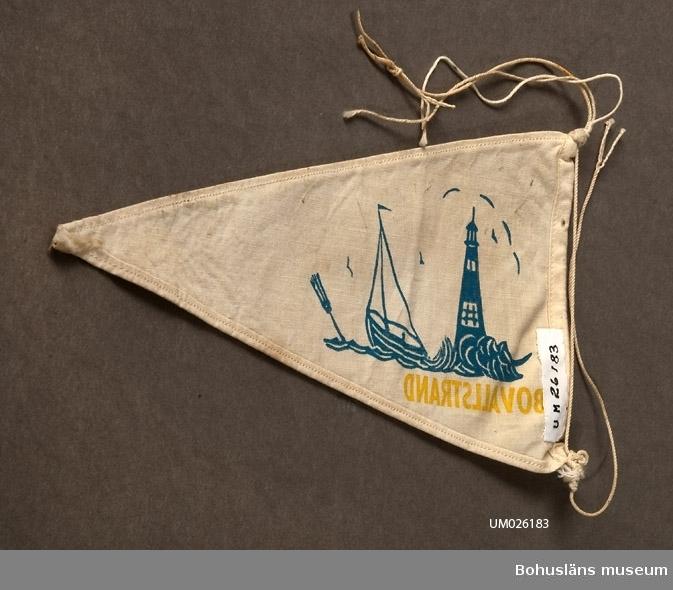 """Trekantig vimpel. Mot naturfärgad vbotten textiltryck. Hav, båt, prick och fyr i blått samt namnet """"Grebbestad"""" i gult. Sammanhör med UM026180-UM026184 Användnings- och förvärvsuppgifter se UM026180"""