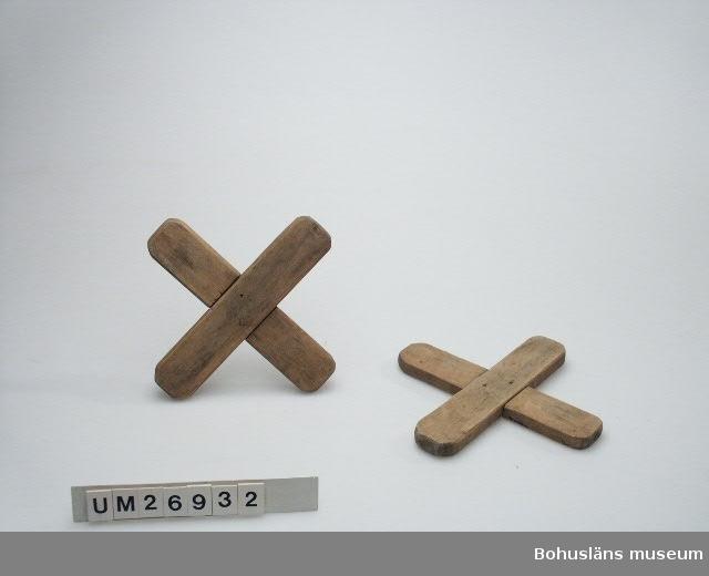 Föremålet visas i basutställningen Kustland,  Bohusläns museum, Uddevalla. 471 Tillverkningstid 1920-TAL? 594 Landskap BOHUSLÄN 394 Landskap BOHUSLÄN  Två stycken omålade träkors, nu grå/brun/beige till färgen. Varje kors är sammansatt av två rektangulära träbitar som är inpassade i varandra på mitten där de är avsågade/ avslagna till sin halva tjockek. Bitarna hålls ihop av två träpluggar på mittpartiet. Träbitarnas hörn är rundade. Skvalpkorsen är använda i hinkar med vatten så att vattnet inte skulle  skvalpa över när man bar dem. De användes så på 1920-talet i Smögen. De fanns förvarade i en sjöbod som syskonen Stranne 1998 höll på att tömma på föremål. Kommentar till beslutet att ta in skvalpkorsen i museets samlingar: De visar hur värdefullt sötvattnet var i kustsamhällena.  Hänvisning till målning CGB180 som visar på användning av skvalpkors.