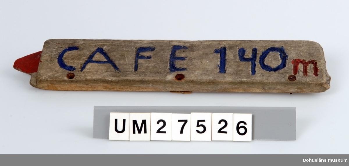Vägskylt tillverkad av elev vid Åstols skola, Tjörns kommun. Vägskylt  tillverkad av en bit drivved. På framsidan inhuggna texten CAFE 140 m, målat i blått och rött samt en pil som pekar åt vänster. Borrhål för skruvar.  Föremålet visades i utställningen Moderna skärgårdsbor på Bohusläns museum 2002. Utställningstext: Vägskyltar Nio skyltar som vägvisare på Åstol. Från affären till rökeriet är det 375 meter och från skolan till badplatsen är det 200 meter. Skyltarna berättar om en liten ö med många mötesplatser. Här finns affär, bibliotek och skola - restaurang, lekpark och flera församlingar. En tätbebyggd ö omgiven av havet, med skolan i centrum - så viktig för barnfamiljerna och åretruntboendet. Skyltarna är gjorda av elever i årkurs 4 - 6 på Åstols skola.  Skylten ingår i insamlingen i projektet Moderna skärgårdsbor, UM27511 - UM27595 och kommer från Åstol.  För övrigt material från Åstol, se UM27524-UM27538 och UM27566-UM27594; UM27524 Tjörn Runt-teckning UM27525- Vägskyltar, 9 st UM27533 UM27534:1-2 Eternitplattor, 2 vita refflade  UM27535 Eternitplatta, 1 vitmålad slät UM27536:1-2 Eternitplatta, 2 gröna UM27537 Cykelkärra UM27538 Matjordsäck, 2 st (omärkt) UM27566- 28 barnteckningar över Åstol, indiv. inv.nr. UM27593 UM27594 Skylt frikyrkan med gudstjänstaffisch Arkivet 9 uppsatser från skolbarnen i samband med teckningarna.  För information om projektet Moderna Skärgårdsbor, se UM27511.  Litt: Sjöholm, Carina. Moderna skärgårdsbor i gammal kultur. Skrifter utgivna av Bohusläns museum och Bohusläns hembygdsförbund nr 73. Bohusläns museums förlag.  Avsnittet om Åstol s. 17 - 45..