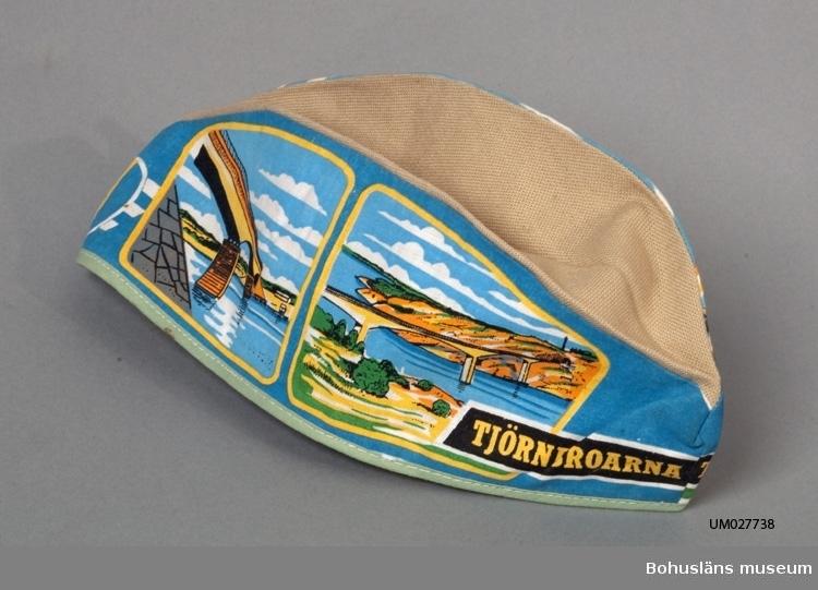 Avlång mössa i båtmössemodell med bälg. Färgtryck i gult, blått, grönt, grått och svart på bomull. Kantad med gönt kantband. Motiv med Tjörnbroleden ur olika perspektiv och texten TJÖRNBROARNA. Föremålet togs fram till invigningen av Tjörnbroarna sommaren 1960 tillsammans med ytterligare några föremål. Beställare och försäljare var Ruckmans Bokhandel HB i Skärhamn. Ruckmans bokhandel flyttade senare till Stenungsunds Torg. Ytterligare föremål, se UM26955 Vykort, UM27736 Kuddfodral och UM27737 Väggprydnad  Litteratur:  Stenungsunds hembygdsförening. Tjörnbroarna 50 år 1960 - 2010. (2010)