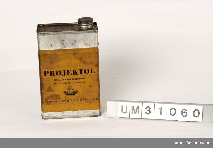 Rektangulär plåtdunk med skruvkork på ovansidan. Klädd med stor pappersetikett som varit rosa, idag inoljad. På etiketten svart text: PROJEKTOL SPECIALOLJA FÖR PROJEKTORER MED CIRKULATIONSSMÖRJNING AB GASACCUMULATOR TEL 65 25 20 RIKS 65 25 40 STOCKHOLM  Dunken innehåller olja.  Oljan är  använd för smörjning av filmprojektorns mekaniska delar, UM31031.  Projektorn är tillverkad av AEG på 1920-talet och har använts i Folkets Hus i Sjöbol vid Lysekil.  Till projektorn hör en lång rad delar och olika tillbehör, UM31031 - UM31062.  För ytterligare upplysningar om filmprojektorn, dess olika delar och använding, se UM31031.