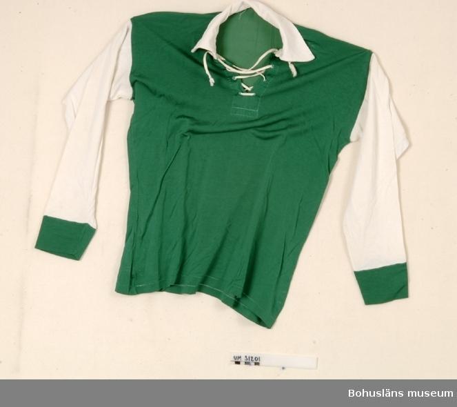 """Mörkgrön fotbollströja i pläterad bomull med långa vita ärmar med gröna muddar, vit krage och fotbollssnörning i halsen med vitt dragsnöre. Snörningen förstärkt undertill med bomullslå. Tröjan är lagad på ett flertal ställen. Ärmlängd 50 cm. Tröjan är använd i  Gustafsbergs IF,  Gustafsbergs skolhems fotbollslag och är från 1950-talet. Givaren har fått tröjan av sin far som var förvaltande direktör på Guastafsberg från 1960-talet. Oklart hur länge GIF fanns. Klubben var inte längre aktiv 1966 när familjen Hernek flyttade till Gustafsberg. Till tröjan hör en klubbnål/klubbmärke, UM031205.  Anders Knape Hansson och hans hustru donerade 1772 större delen av sin betydande förmögenhet till Gustafsbergs barnhus. Barnhuset eller internatskolan startade 1776 och drevs fram till 1920-talet. Skolhuset gjordes då om till badhotell. Det skulle finnas högst 25 pojkar vid skolan och de skulle lämna den vid 16 års ålder. Gustafsbergs Skolhem  öppnades 1949 och drevs fram till 1979. Eleverna bodde då återigen i stora huset. Därefter har stiftelsens ändamål bl. a. varit att förvalta kvarlåtenskapen i den anda som kommer till uttryck i makarna Knape Hanssons testamente så att man med avkastningen ekonomiskt kan stödja studerande ungdom från Bohusläns. Detta sker numera med en årlig utdelning av stipendier.   Inför öppnandet av Gustafsbergs skolhem 1949 byggdes det gula annexet där kök, matsal och några personallägenheter låg. Här bodde husmor.  Skolhemmet var avsett för de pojkar som saknade läroverk eller gymnasium på hemorten. Här gick också flera pojkar som kom från små ekonomiska förhållanden men som fått stipendium för att kunna läsa vidare. Det var vanligt att dessa pojkar stannade kvar på Gustafsberg över helger och lovledigheter.   """"Det var lite synd om Gustafsbergspojkarna"""", berättar några anställda vid museet som har haft flera klasskamrater som bodde här.  Det finns en förening, Gamla Gustafsbergspojkar, som träffas regelbundet. Det finns också personer som inte vill delta"""