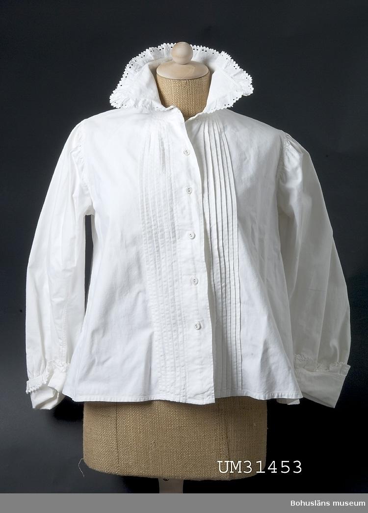 Enkel vidd nertill: 73 cm, Ärmlängd: 44 cm.  Långärmad blus av vit bomull med knäppning fram. Hög krage med breda snibbar. Stråveck på framstyckena. Längs krage och ärmslut påsydd maskinväd vit bomullsbrodyr. Rynkad ärm med extra långa manschetter. Klädda vita knappar.  Blusen är extra vid runt magen. Välsydd.  Blusen är tillverkad av Anna Olsson, född 1880, hemsömmerska, gift med Hilmer Olsson, fiskare f. 1874. Familjen bodde på Smögen. Anna och Hilmer hade fem barn. Anna sydde alla kläder till barnen och även till släkt och vänner. Anna hade en bror vars fru dog då deras fyra barn var 2, 4, 6 och 8 år gamla. Anna sydde alla kläder även till dem. Anna hade ingen formell yrkesutbildning men lärde dig av andra sömmerskor.  Denna blus, samt en snarlik (UM31453) använde Anna efter det att barnen fötts hemma, vilket var det vanliga vid denna tid. Mödrarna låg ofta till sängs en tid efter förlossningen. Ett vanligt samtalsämne mödrar emellan var de stickningar man kände i fötterna när det var dags att stå upp. Dessa blusar var tillverkade med extra omsorg för att man skulle se så fin ut som möjligt då man sängliggande tog emot besök av släkt och vänner.  Anna och Hilmers barn föddes 1904 (Olle), 1906 (Ruth), 1908 (Henry), 1910 (Artur) och 1917 (Maria, gift Rödström).  Maria Rödström, gift med Karl-Olof Rödström, f. 1916. Karl-Olof Rödström son till och Evert Rödström, f. 1898 och Irene Rödström (1903 - 1995). Evert och Irene är också föräldrar till Karin Rödström.  Evert är bror till Gertrud Linnea Gunnarsson, f. 1896 med dottern Berit Gunnarsson, f. 1922. Evert och Gertrud Linneas föräldrar är Frans Rödström, f. 1871 och Sofia Rödström , f. 1872  Se flera föremål från Smögen i samlingarna från denna Smögenfamilj.