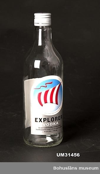 """Vodkaflaska Explorer. Konisk flaska i klart glas med två pappersetiketter,  förslutning med grå skruvkork med ett råsegel. 37,5 %VOL. 700 ml. Flaskan är tom.  På etiketten ett  fyllt röd- och vitrandigt vikingatida råsegel mot blå bakgrund, en röd fladdrande vimpel med omramande texten: """"KORSADE ATLANTEN 1958 OCH TOG SVERIGE MED STORM 1961"""" samt EXPLORER VODKA En ren kvalitetsprodukt destillerad från hundra procent utvalt vete av högsta kvalitet. 37,5 %VOL 700 ML På baksida etikett med färgfoto på drinken  EXPLORER ALLAN och hänvisning till www.explorervodka.com för ytterligare recept.   Flaskan visades i utställningen Vin, sprit och riktiga karlar på Bohusläns museum sommaren 2009. Genom att dricka Explorer signalerar man att man dricker för att bli full.  Flaskan är funnen bakom museet. Problemen med missbrukare som uppehåller sig runt museet är ett eskalerande problem som pågått länge."""