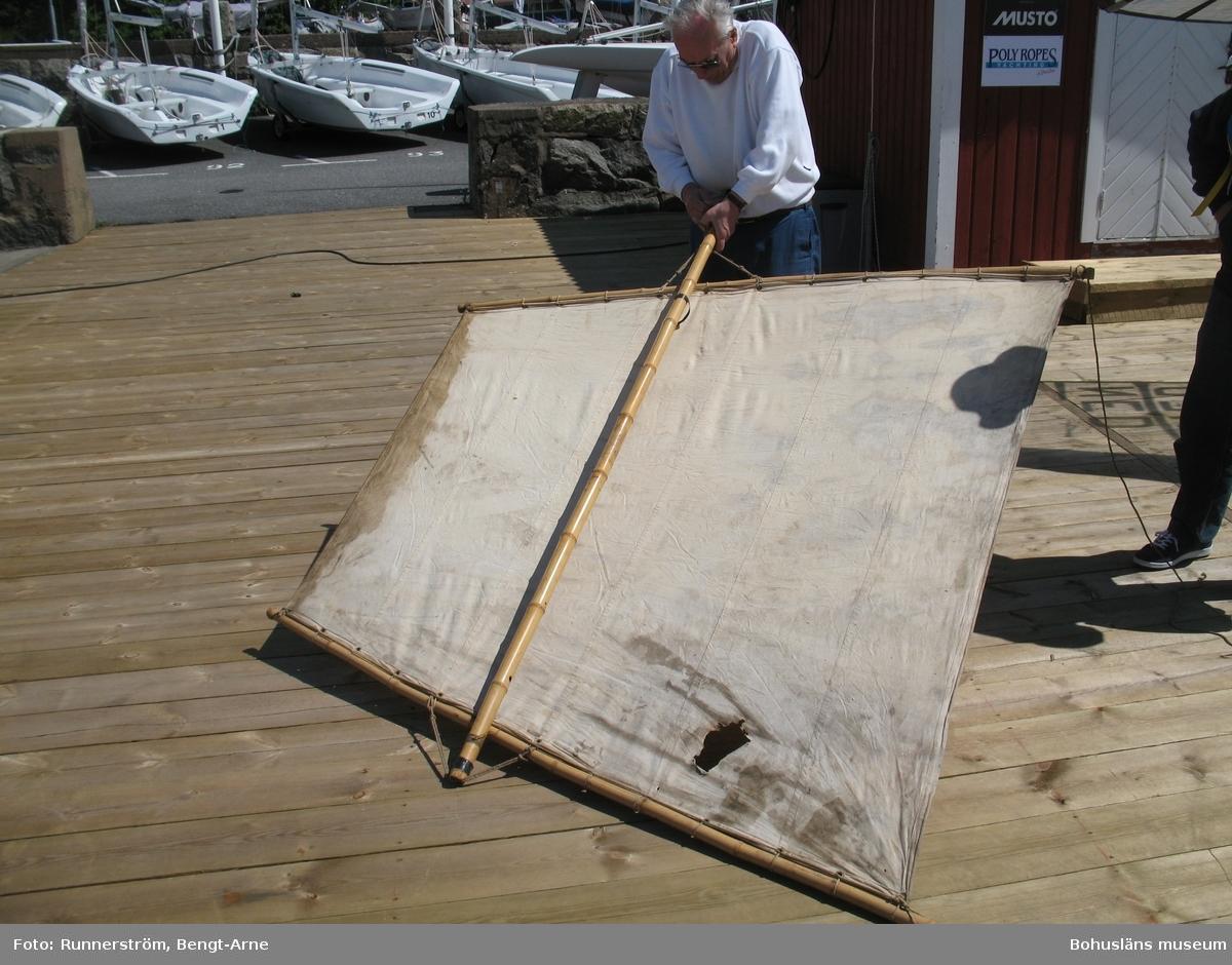 Draksegel av bomull  med rigg av kraftig bambu. Femhörnigt segel, litsat runt akterrån och utspänt längs bom och två främre rår fastsurrade i varandra och bommen.