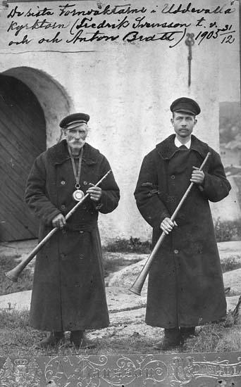 """Text på kortet: """"De sista tornväktarna i Uddevalla kyrktorn (Fredrik Svensson t.v. och Anton Bratt). 1905 31/12. 1905: Tornväktare i Uddevalla, som med 1906 års ingång komma att tillhöra det Uddevalla som gått.  Tutningen upphörde 31/12 06 men nattvakterna i tornet pågingo ändå t o m 31/12 07 då all vakt i tornet upphörde""""."""