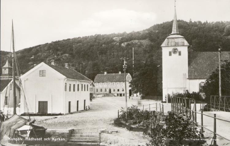 """Tryckt text på kortet: """"Kungälv. Rådhuset och Kyrkan"""". """"21 OKT.1956""""."""