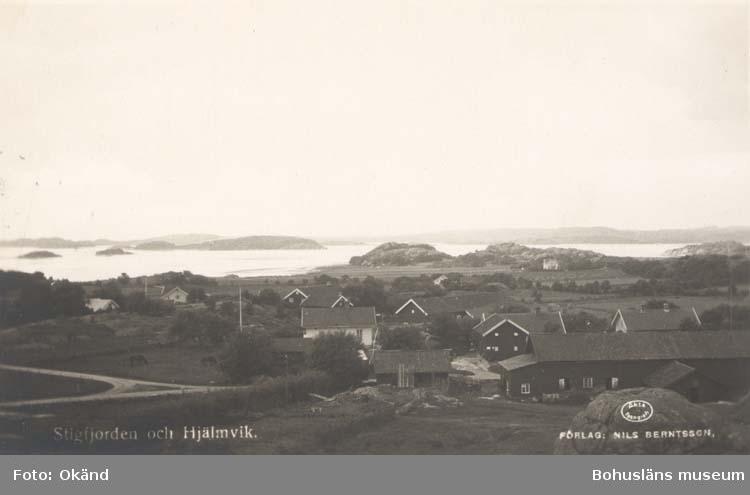 """Tryckt text på kortet: """"Stigfjorden och Hjälmvik."""" """"Förlag: Nils Berntsson."""" Noterat på kortet: """"Hjälmvik Stala Sn. Tengeby (Orust)."""" """"Utsikt ssv. mot Kalvöfjorden.."""" """"26 Aug. 1955."""""""