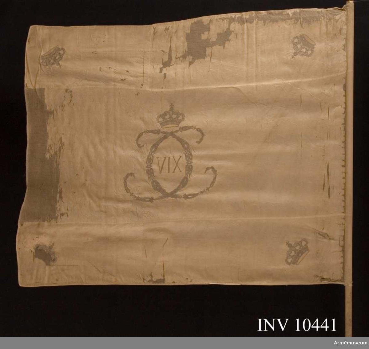 Grupp B I.  Fana vid Svea livgarde under Karl XIII:s och Karl XIV Johans regering. Fanduk av vit sidenkypert varå broderat omvänt lika å båda sidor med guld. Karl XIII:s (XIV) namnchiffer, dubbelt av små ornament bildat C under sluten krona med rött foder, pärlor i silver, stenar i olikfärgat silke. I hörnen liknande kronor, kantad med vitt sidenband, fäst med liknande band och förgyllda spikar. Övre, yttre kronan saknas. Stång av vitmålad furu, avsågad. Fanspets Karl XIV Johan.