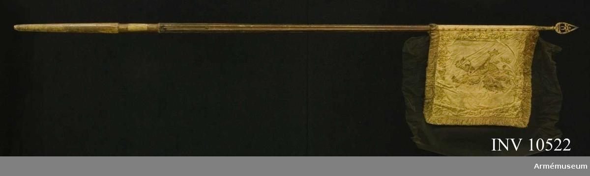 """Grupp B.  Duk av röd, stormönstrad dubbel sidendamast, fodrad med grovt lärft. Målat å inre sidan en gyllene, rödskuggad grip (Östergötlands sköldemärke). Utmed kanten bård av stiliserat bladverk, kronor och korsade palmkvistar i rödskuggat guld. På yttre sidan Carl XI:s namnchiffer - ett dubbelt C under sluten kunglig krona, prydd med pärlor i silver och stenar i rött och grönt. Bården liknande sidans, allt i rödskuggat guld. Kant av 50 mm bredd, frans av rött silke och guld.  Duken fäst vid stången med tre rader förgyllda mässingsspikar.Stång av furu, målad rödbrun ovan greppet, fyrrefflad, förstärkt  med järnskenor, löpande bärring. Längd till duken 540 mm, till greppet 2075 mm. Handgreppets  längd 220 mm. Totalt 2880 mm. Spets av järn, förgylld. Bladet prytt med ett dubbelt C under öppen krona; h:240 mm, holk 110 mm.Tillstånd: Duken mycket blek och färgen till stora delar  bortfallen. Stången avsågad nedtill och återstoden ganska nött. Banderollen saknas. Östgötavapnet silverrosor utelämnade. På greppet ett papper med inskrift """"Lifrustkammaren 251""""."""