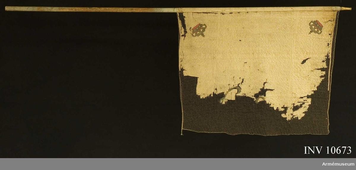 Grupp B.  Duk med Karl XIII:s namnchiffer ändrat till Karl XIV Johans. Fana för Livgrenadierregementetes rusthållsdivision, senare Andra livgrenadjärregementet. Duken av vit sidenkypert varå broderat i guld omvänt lika å båda sidor Karl XIV Johans namnchiffer, av småornament bildat dubbelt C varinom XIV. I hörnen slutna kungliga kronor med rött foder. Kantad med vitt sidenband och fastsatt med förgyllda spikar, därunder vitt sidenband. Stången av furu är vitmålad. Holk av förgylld mässing, 82 mm. Stångens diameter ovan fanan 38 mm och nedanför fanan 40 mm. Spetsen saknas.