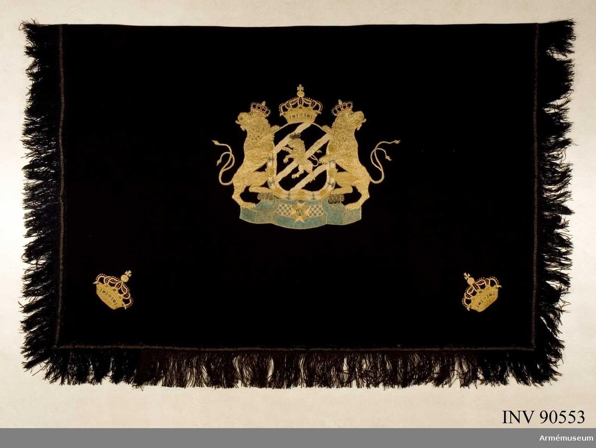 Höjd med frans 106 cm, bredd 170 cm. Av svart kläde med kantfrans av svart ylle samt kungl. Göta Gardes vapen och två kungliga kronor broderade i gult silke. Rektangulär form.  Fem stoppar vid överkanten. Tillhört kungl Göta garde  (1792-1806).