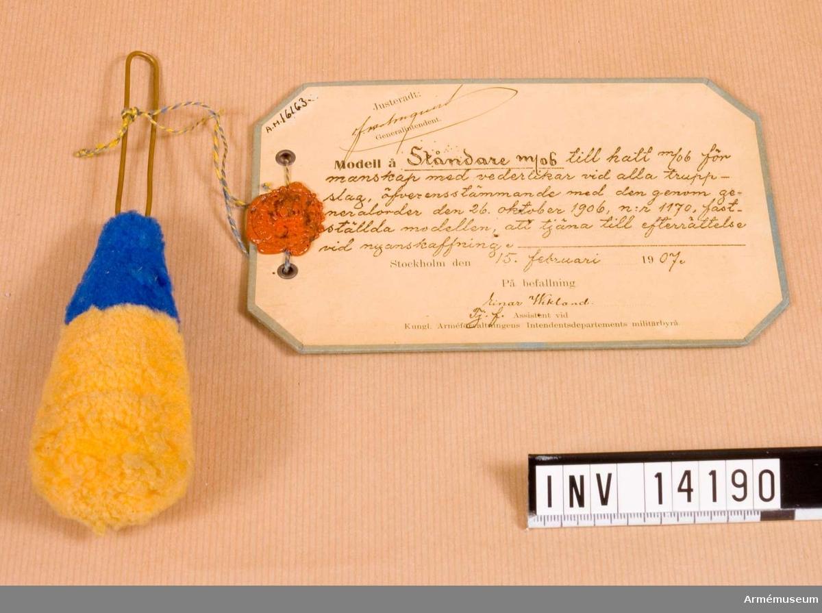 """Grupp C I. Vidhängande modellapp med text: """"Modell å ståndare m/06 till hatt m/06 för manskap med vederlikar vid alla truppslag, öfverensstämmande med den genom generalorder den 26 oktober 1906, n:r 1170, fastställda modellen, att tjäna till efterrättelse vid nyanskaffning. Stockholm den 15 februari 1907. På befallning, Einar Wikland Tj. f. Assistent vid Kungl Arméförvaltningens Intendentsdepartements militärbyrå."""""""
