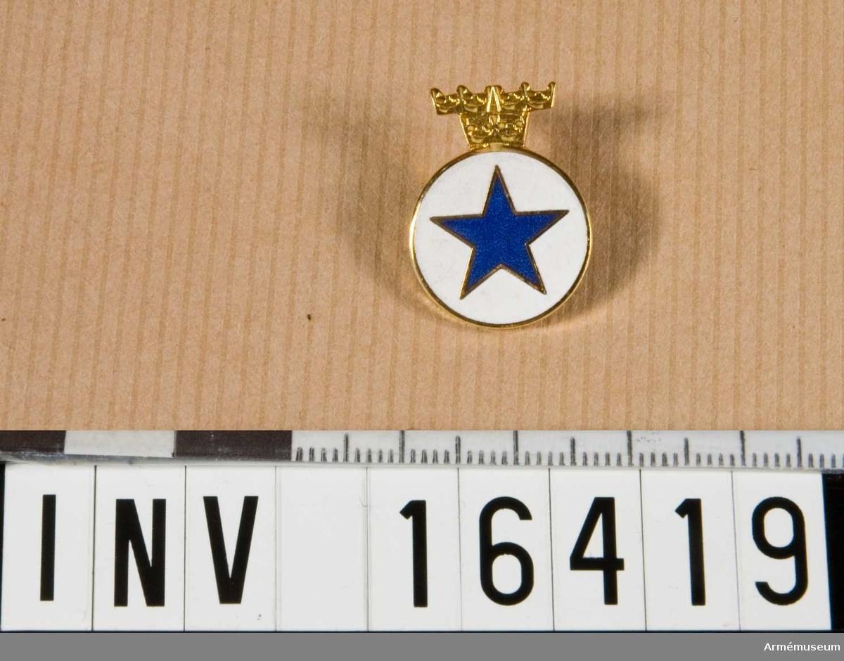 """Personalkårstecken m/1941, Blå Stjärnan.Femuddig, blå stjärna på vit plan, rund botten. Smal guldkant runt stjärnan och rundeln som är krönt av """"tre kronor"""" i guld. På baksidan en vågrät broschnål och text """"Svenska Emaljarbeten""""Skänktes till museet efter utställningen """"Svenska Blå Stjärnan 70 år"""" 1987-04-26--09-25."""