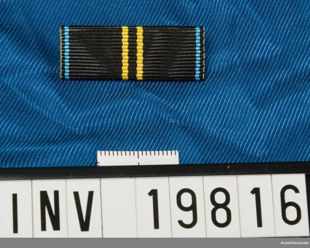Svart band med två gula streck på mitten och ett blått streck på vardera kanten. Släpspännet förvaras i en ask tillsammans med en medalj och en miniatyrmedalj.