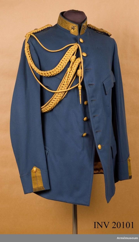 Grupp C I. Ur uniform för officer, general, i persiska armén. Består av mössa, vapenrock, långbyxor, kappa, aiguilette, epåletter.Kollett av ljusblått kläde. Enradig med 8 knappar. Axelklaffar av guldtränsar med valknut och stor femuddig stjärna. Foder av grå siden. Knappar av gul metall med persiska emblem, lejon med svärd och krona ovanpå och två kvistar under lejonet, d:25 mm: 8 på bröstet, 2 vid ärmen. Krage, upprättstående, med raka vinklar. Fodrad med svart bomullstyg. Runt kragen guldgalon, b:40 mm. Den pryds med 2 stora, femuddiga silverstjärnor. Ärmuppslag, spetsiga. 120 mm höga framtill. Vardera har upp- stående knapphål av guldgalon, b:30 mm, jämte vid övre spetsiga galon av knapphålet, en stor knapp.