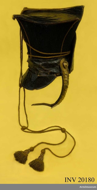 Grupp C I. Tidigare Storfurst Tsesarevitsch Konstantin Pavlovitsch ulanregemente. Ulanmössan består av två delar: övre delen, fyrkantig av blått kläde, betäckt med läder. Hela övre delen är prydd med gula snören. Nedre delen: av läderlister, 7 cm breda. Lädret är svartlackerat. På framsidan är fastsydd en skärm av  lackerat läder och på baksida finns en halvoval läderlapp, nackskydd. Foder av grovt linnelärft. Etischkett- Aiguillette -ägiljett, l:120 cm, av gula garnsnören med två tofsar. Hakrem, defekt, av mässingsplåt. Endast högra sidan finns kvar. Litteratur: Knötel-Sieg, Handbuch der Uniformenkunde, Hamburg, sidan 332: Ulanernas tscapka var av blått kläde. Livgardets ulaner hade från år 1803 revär av blått kläde på tscapkan. F. von Stein, Geschichte des russischen Heeres, Hannover, 1885, 11 sep. År 1803 grundades Storfurst Konstantin Pavlovitsch Ulaner, vilka sedan fingo bära Livgardets ulanbenämning. Deras sista hederschef var kejsarinnan Alexandra Feodorovna. Krigsenziklopedi, S:t Petersburg, 1912, Del VIII, sidan 384: År 1808 infördes i ulanregementerna tschapkan med läderbotten 35 cm bred och med 7 cm läderlister på nedre delen, prydd med gula snören.