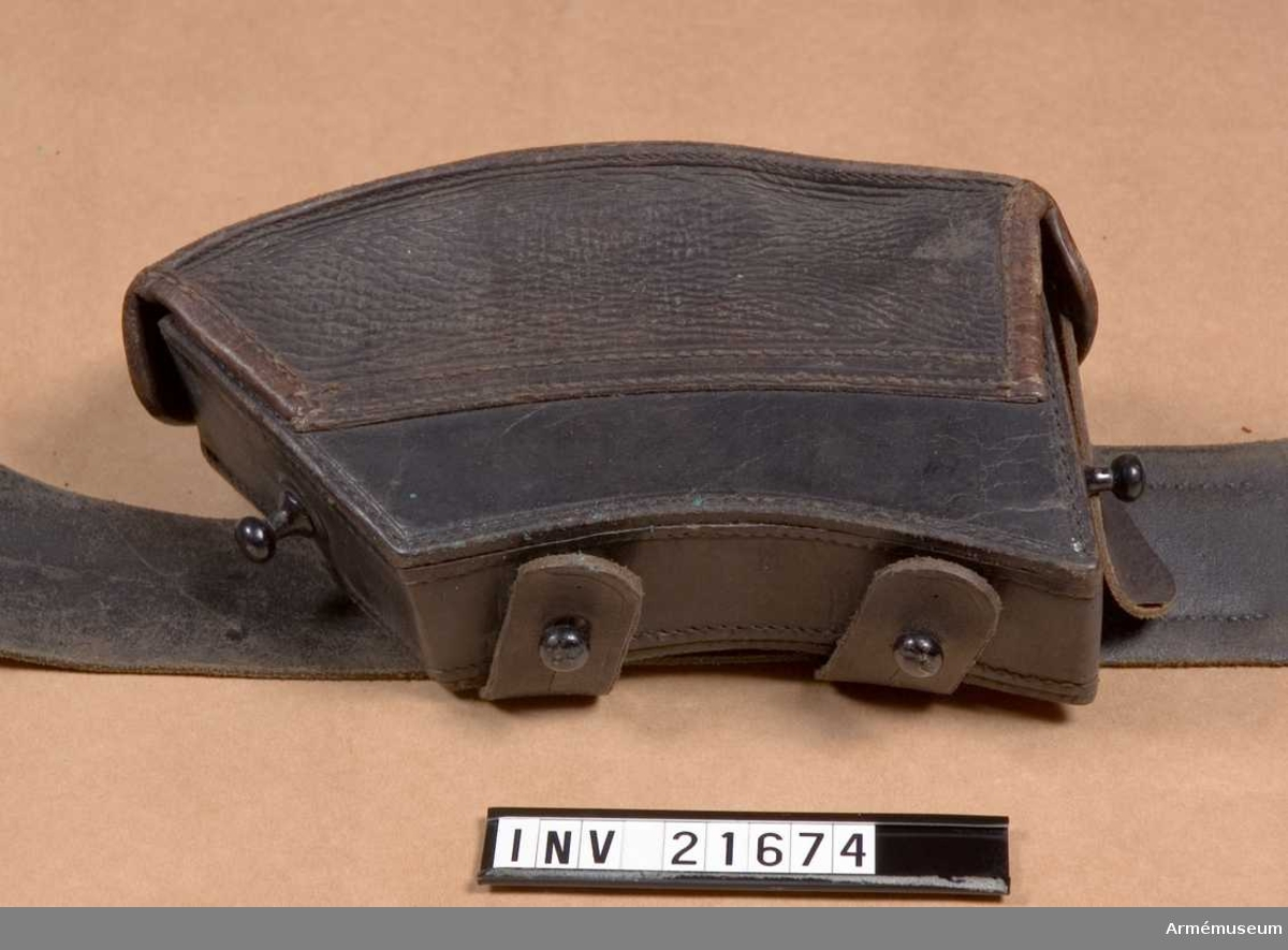 """Grupp C I. Av svart målat läder till 8 mm """"Repetitions""""- gevär (mod. 1888) för 20 patroner.  LOCK som stänges på sidorna med två metallknappar; på lockets insida stämplar: """"B & Co"""", """"M D 1"""" =Munitions Depot N 1, """"1888"""", """"W S"""".  VÄSKA med på baksidan två hylsor av samma läder med knapphål på ändarna, att knäppa till metall knappen på väskans yttre bottensidor och på dess baksida en ring att koppla till tornistremmar. I väskan en träbit att hålla 2 patronaskar i ordning.En pappersetikett med text """"Muster"""". """"Patrontasche für 8 mm Repetirgewehr Munition für Infanterie und Jäger, mit Gewehr."""" """"Ausgefertig beim K.K. Montur Depot N 1 in Brünn auf Grundes Reichs Krieges Ministerial Erlasses von 12 juni 1988. Abteilung 13. No 1042."""" På etikettens baksida rött sigill med påskrift """"K.L. Monturs Depot N 1 zu Brünn"""". LITT  Enl. Österreich-Ungern. Das Heer E. von Zapelin 1898. Sida 200. År 1888 infördes i österriska-ungerska armén s.k. """"Repetier Gewehr"""" med kaliber 8 m/m (tidigare 11 mm)."""