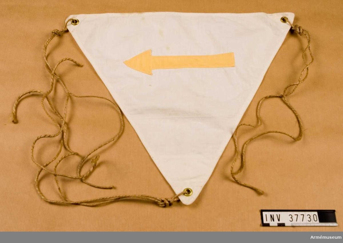 Grupp H I.  Vit, trekantig skylt, 40x40x40 cm, med en gul pil. I vart hörn ett öljetterat hål för snöre.  Vidhängande snöre.M 7611-212010, f.d. Tc 29023.