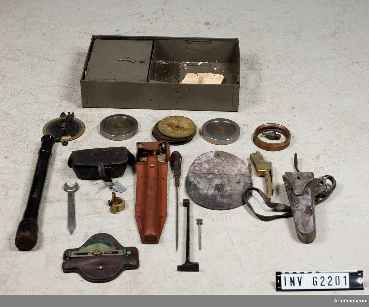 Grupp F I. Lådan innehåller 5 st filtskivor, 6 st fänghålstätningar av  koppar, 2 st fänghålsskruvar, 6 st läderringar, 1 st korn, 2 st  stötbottnar, 2 st tätringar, 4 st undeläggsskivor av metall,  nyckel till mekanism, nyckelskruv till fänghålsskruv och  korn, riktbåge med fodral, riktdiopter med fodral, rymnål,  siktdiopter, sättare, tändrörsväska med rem och upprymningsstål.