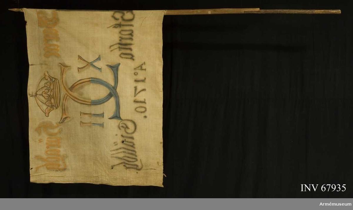 Duk: Tillverkad av enkel vit linnelärft, sydd av två horisontella våder som kastats samman. Den vertikala kantfållen lagd mot dukens utsida.  Dekor:  Målad endast från dukens insida. Karl XII:s namnchiffer dubbelt C med X-II på ömse sidor, krönt med sluten krona, upptill i gult och brunt nedtill i blått och svart. Text på ömse sidor om chiffret, upptill i gult och nedtill i svart, under detta text i svart.  Duken fäst vid stången med en rad järnspik på en läderremsa, saknas bitvis upptill och nedtill. Stång av trä. Övre delen fasetterad.