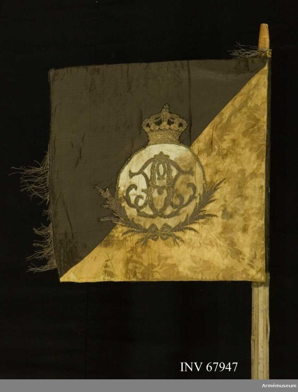 Duk: Tillverkad av dubbel damast, det svarta fältet med taft, vapensidans svarta fält med atlas och gula fält med sidenkypert. Duken fäst vid stången med tre rader tennlikor på gula sidenband.  Dekor:  Diagonalt delad i två fält på inre sidan, det övre svart, det nedre gult med broderat upprätt lejon i guld och svart med guldkontur på det gula, följt av två rosformiga stjärnor i silver (Västergötlands vapen).  På den yttre sidan det nedre inre fältet gult, det övre yttre svart, samt i guld inom krans av palmkvistar, nedtill hopknutna, A med dubbelt F (Adolf Fredriks namnchiffer) på ljusblått fält (numera bara fragment av det blå); över kransen sluten kunglig krona.  Frans:  Spår av guldfrans längs den vertikala kanten.   Stång:  Tillverkad av trä, kannelerad, vitgråmålad; löpande bärring, saknar holk och spets.   Etikett med text på stången.