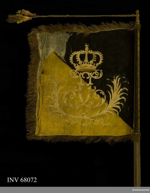 Duk: Tillverkad av dubbel sidendamast, diagonalt delad i två fält, det övre, inre svart, det nedre, yttre gult. Duken fäst vid stången med tre rader tennlickor på gula kypertvävda band.   Dekor: Broderat på inre sidan upprätt lejon i påsydd atlas, gult på det svarta, svart på det gula, med modellering i silke, följt av två stjärnor i gult silke på det svarta fältet, på yttre sidan i plattsöm med vitt (?) silke Fredrik I:s namnchiffer, dubbelt F, krönt av sluten krona, i båge därunder två korsade, hopknutna palmkvistar.   Frans: Dubbel, av silke (bäst bevarad på dukens insida).  Stång: Tillverkad av trä. Kannelerad, gråmålad och snett avsågad. Holk i förgylld mässing.  Banderoller: Tillverkade av svart och gult silke: två snoddar med två tofsar, de senare slitna.