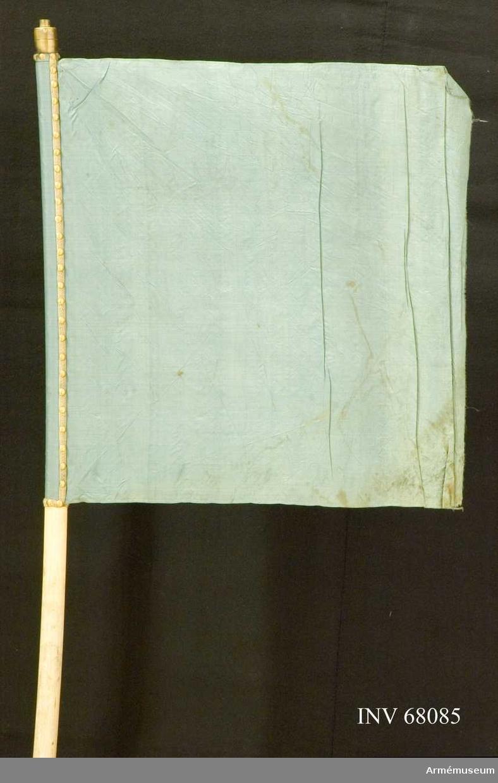Duk: Tillverkad av enkel, blå sidentaft. Duken fäst med en rad tennlickor på ett brett, svagt gråblått band.  Dekor: Saknas.  Stång: Tillverkad av trä, vitmålad, krum. Holk av mässing.  Skinnremmar: En övre, vit skinnrem fäst vid stången på 710-730 mm längd från dukens nedre fäste mätt saknas. Märken efter fäste vid stången på 55-70 mm längd från stångens nedre ände mätt.