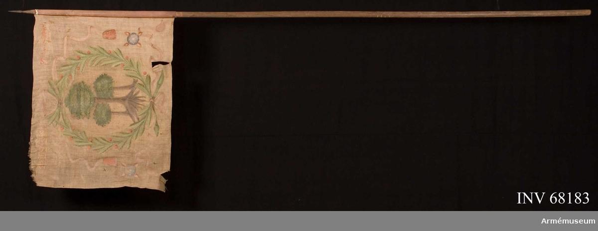 Duk: Tillverkad av enkel vit linnelärft, sydd av två horisontella våder. Kastfållen lagd åt dukens insida. Fäst vid stången med små järn och mässingstennlickor.  Dekor: I mitten Karl XII:s namnchiffer krönt med sluten krona, dubbelt C, på ömse sidor om detta X-II. I den övre våden i gult och brunsvart, nedre våden i blått och svart.   Text på ömse sidor om chiffret, upptill i gult och nedtill i svart. Under chiffret text i svart.  Stång: Tillverkad av trä. Avsågad upptill och nedtill.